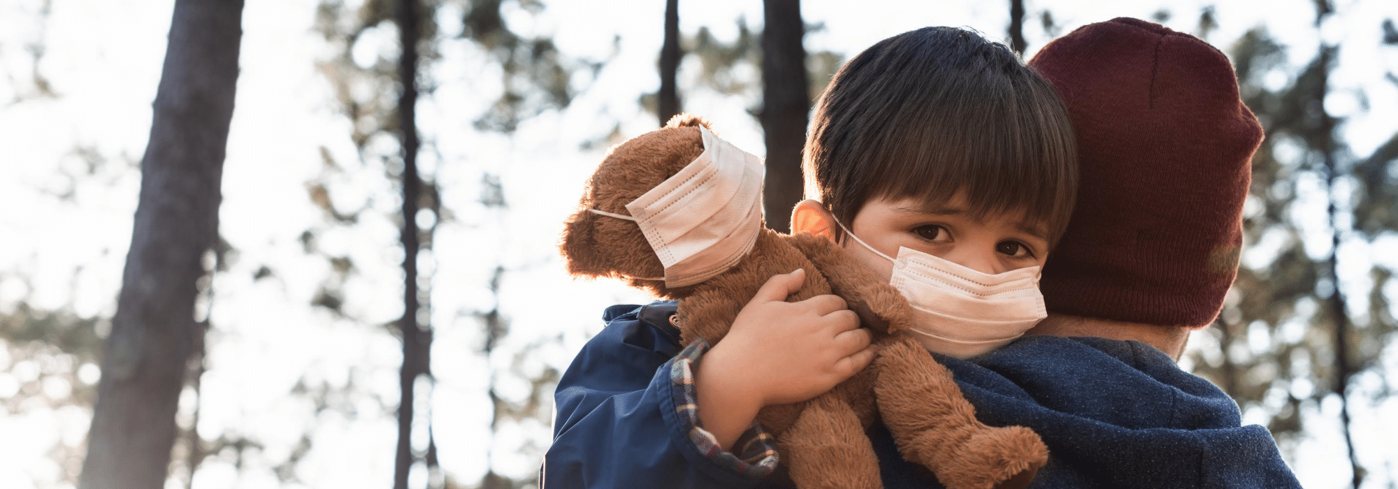 Child and his stuffed bear, both wearing facial coverings.